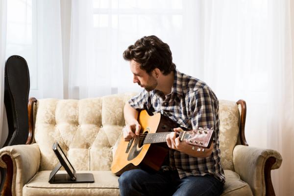 Mann lernt digital Gitarre zu spielen