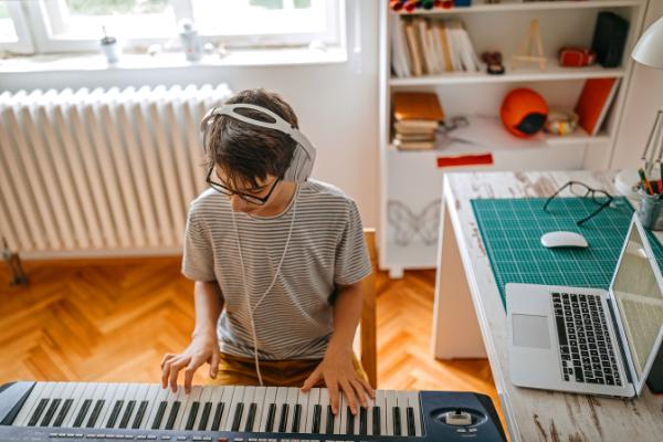 Jungendlicher lernt online Keyboard spielen