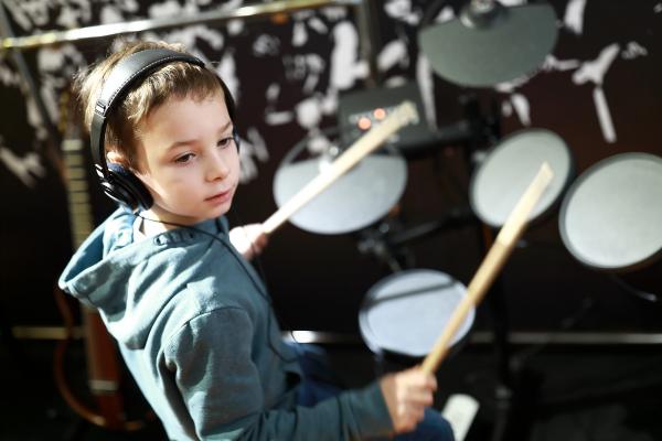 Kind lernt e Drums zu spielen