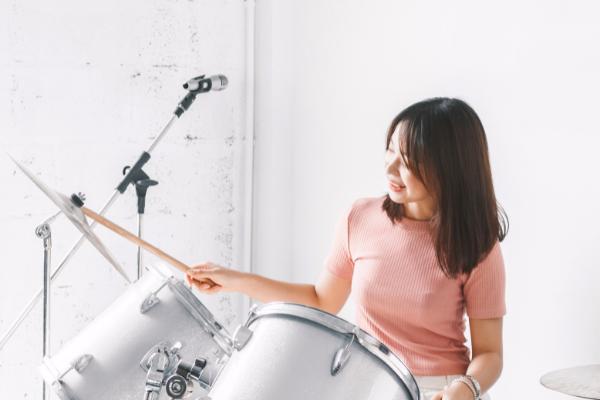 Schlagzeugerin vor weißem Hintergrund